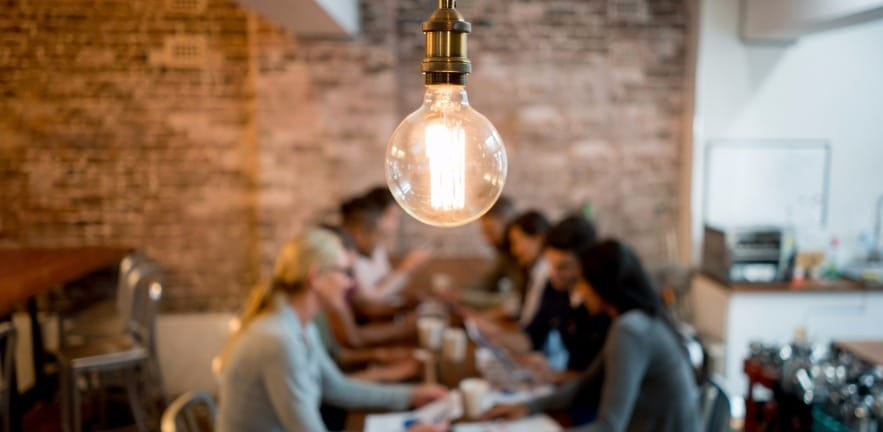 Small business jumpstart - glowing lightbulb with office workers in background