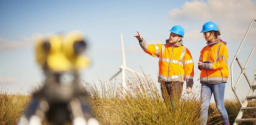 Two wind farm engineers using a builder's level to plan out the expansion of the wind farm site.