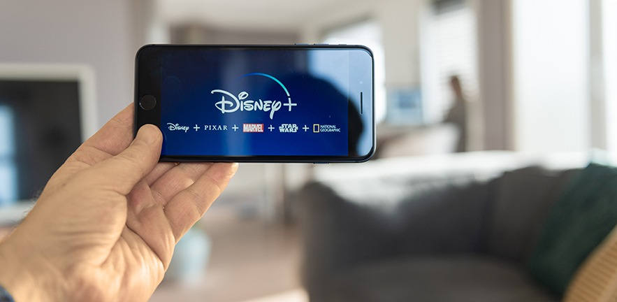 Someone holding up their mobile phone ready to stream Disney +.