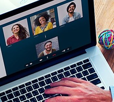Laptop showing a video chat with a few different people.