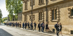 MBA students walk down a street behind Pembroke College in Cambridge.
