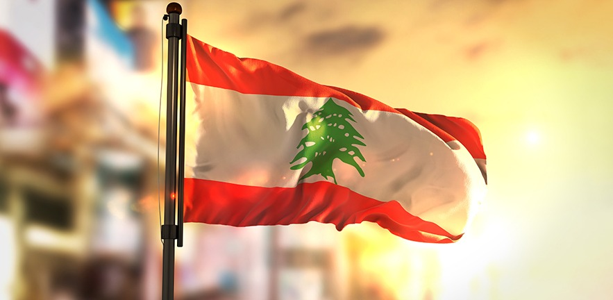Lebanon Flag Against City Blurred Background At Sunrise Backlight.