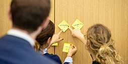 Image of three people completing a group exercise using sticky notes on a wall.
