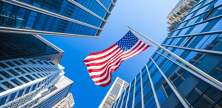 USA flag and contemporary glass architecture of Financial District, New York City, USA.