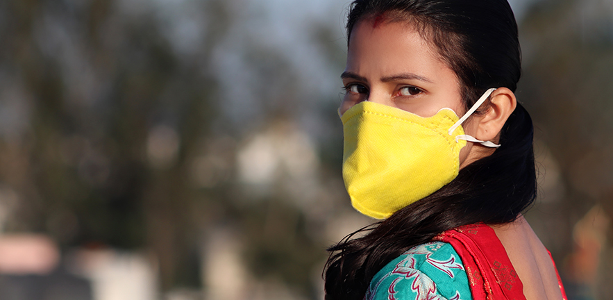 Young Indian women wearing pollution mask against Coronavirus or COVID-19 and standing on rooftop at home in Delhi, India.