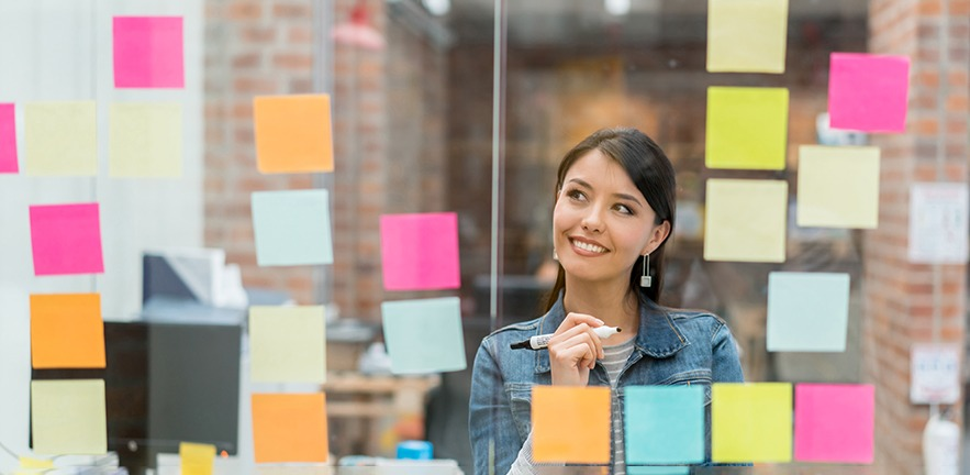 Woman gazes thoughtfully at colourful post-it notes on the glass wall in front of her as she thinks about the future.