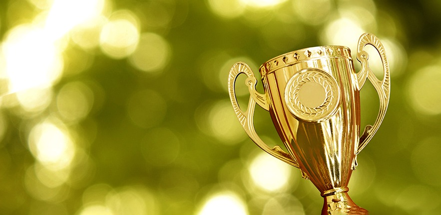 Gold trophy against a soft focus green nature background.