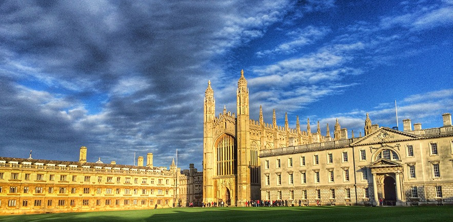 Sun shining on King's College, skies above full of scattered clouds.
