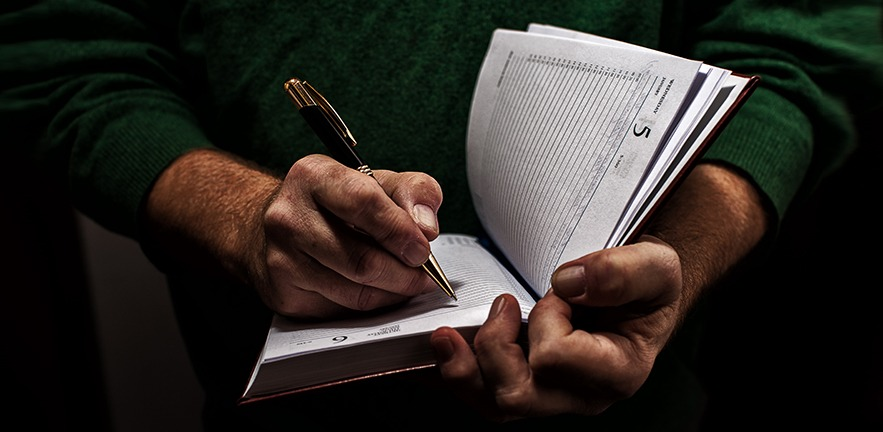 Close up of a man writing in a diary with a pen.